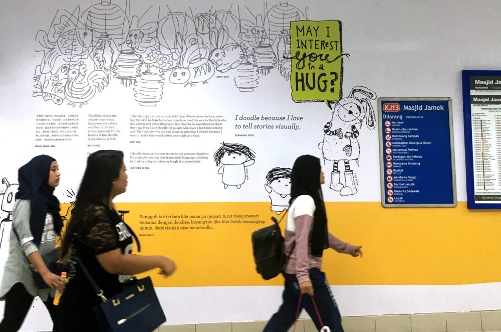 Commuters walking past a section of Masjid Jamek LRT's tunnel wall. Image credit Allie Hill.