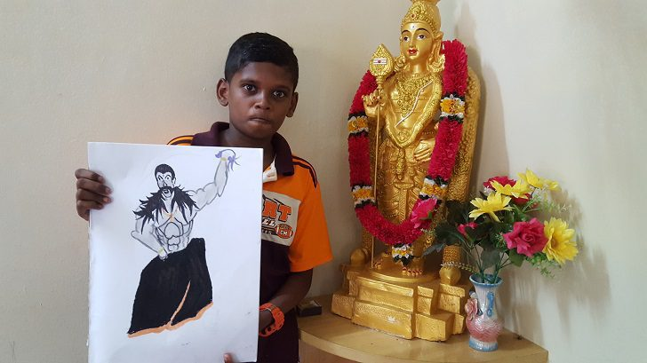 Navien with his first artwork next to his favorite deity, Murugan.